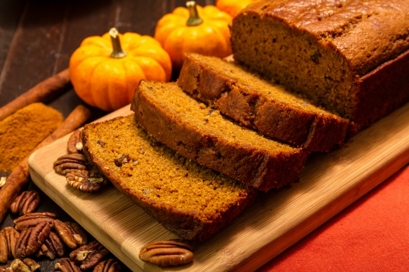 Sliced pumpkin bread loaf sitting on wooden cutting board with pecan nuts and cinnamon spices
