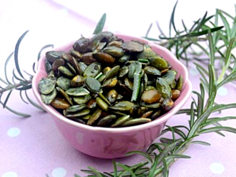 Freshly roasted pumpkin seeds with rosemary
